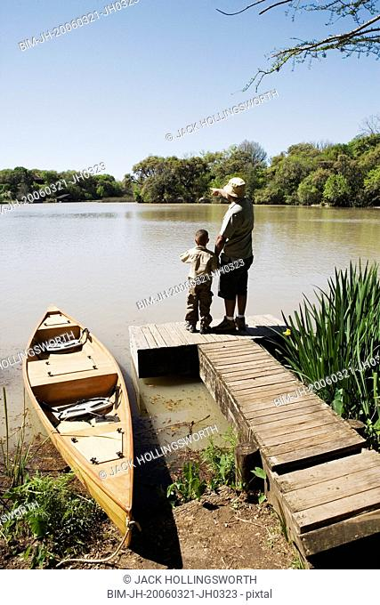 Father and son standing on dock