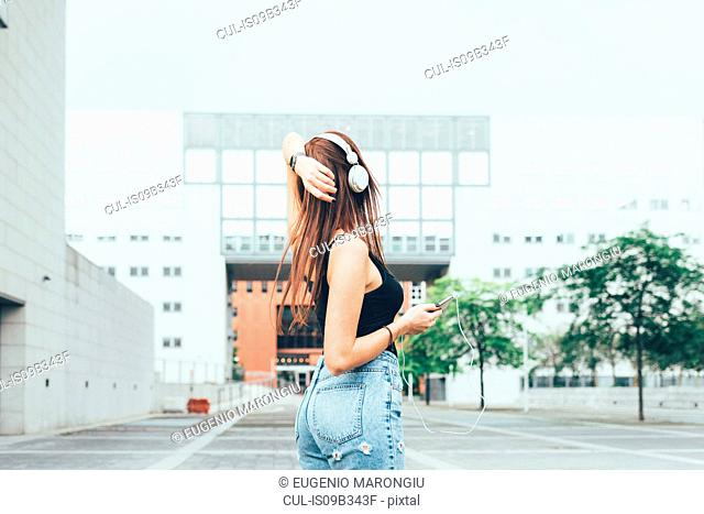 Young woman listening to headphones with hand on head outside office building