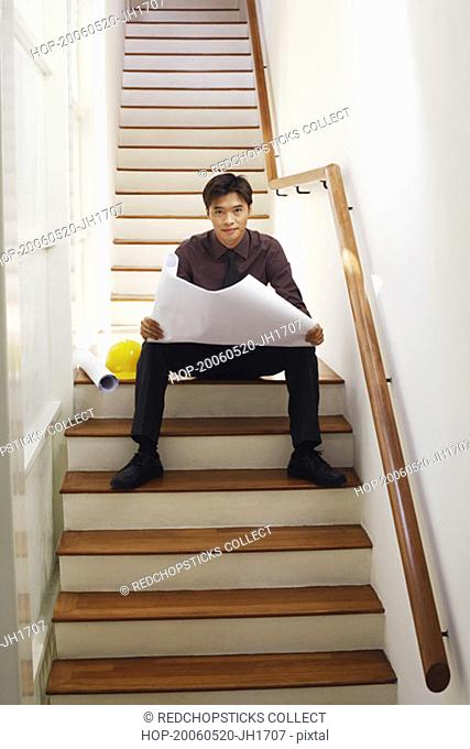 Portrait of a male architect holding blueprints on a staircase