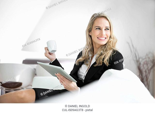 Mid adult businesswoman relaxing with digital tablet and a coffee