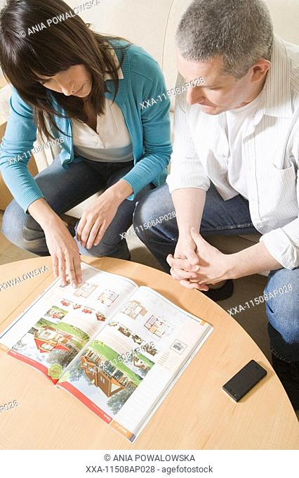 mature couple watching catalogue with houses