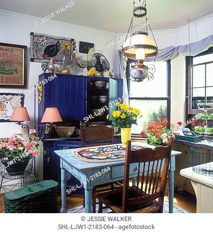KITCHENS: Eclectic, vintage farm and folk art, distress painted cabinet in dark blue, distressed pale blue farm table, hooked rugs decorate the wall and table