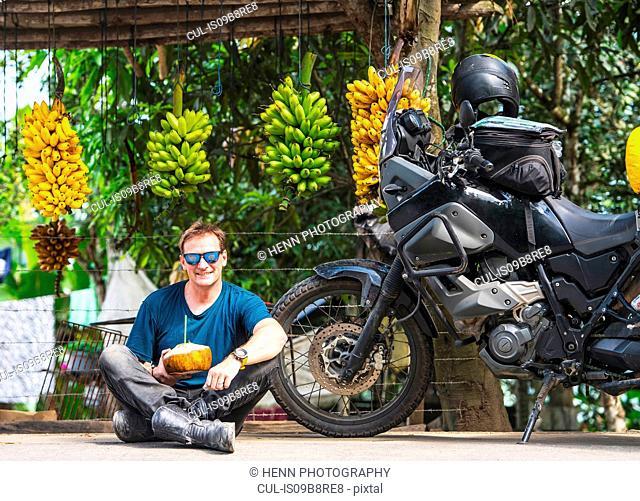 Motorbike rider enjoying local fruit, Machala, El Oro, Ecuador, South America