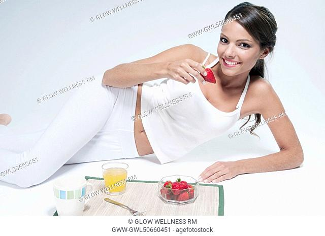Woman lying on the floor and eating strawberries