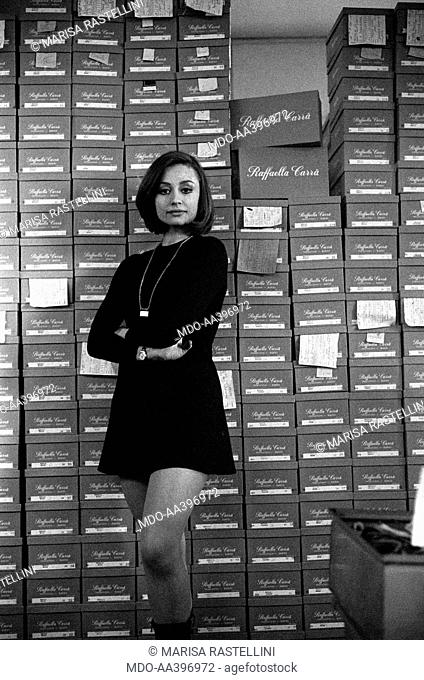 Raffaella Carrà in front of some shoe boxes bearing her name. Italian TV presenter and showgirl Raffaella Carrà (Raffaella Roberta Pelloni) posing in front of...