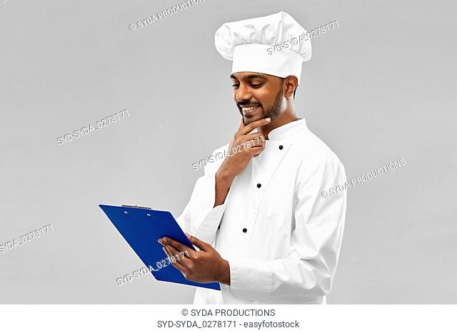 happy indian chef reading menu on clipboard