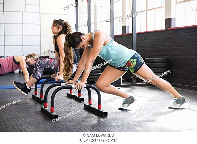 Young woman stretching legs at equipment in gym