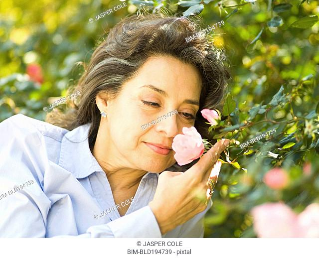 Caucasian woman smelling flower outdoors
