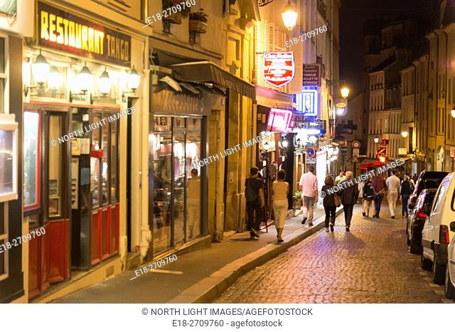 France, Paris. Rue Muffetard. Tourists and local people stroll on popular Parisian street where many restaurants and bars are located