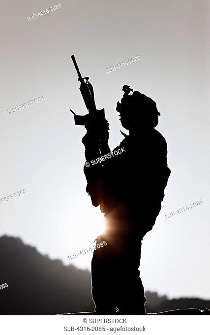 U.S. Army Soldier Holding His Weapon at Sunrise