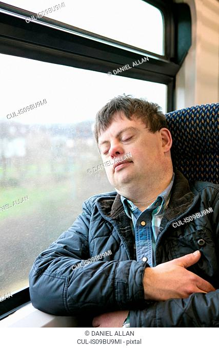 Man with down syndrome sleeping on train