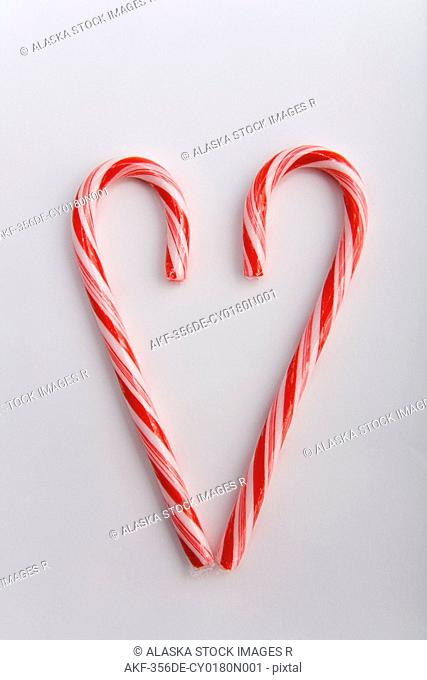 Closeup of two Christmas candy canes in the shape of a heart blurred at top on white background studio portrait