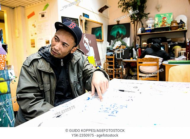 Rotterdam, Netherlands. North African artist, wearing a winter coat and cap, working on a sketch on the main production table of Via Kunst Studio's