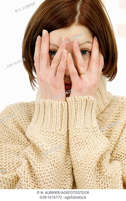 Young woman in a beige turtleneck pullover, looking through her fingers because she is shy or afraid or stressed