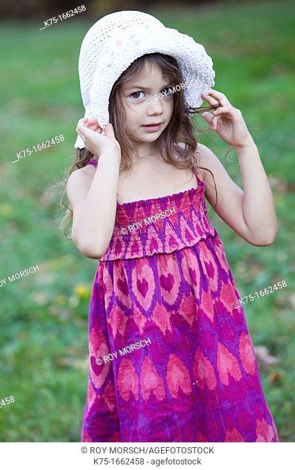 Little girl holding her hat on her head