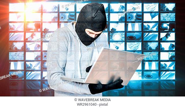 Hacker wearing monkey cap while using laptop