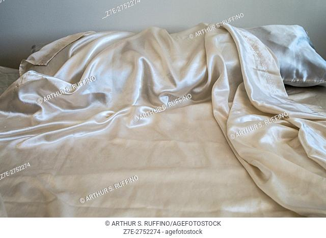 A white sensibility, partial view of an unmade bed