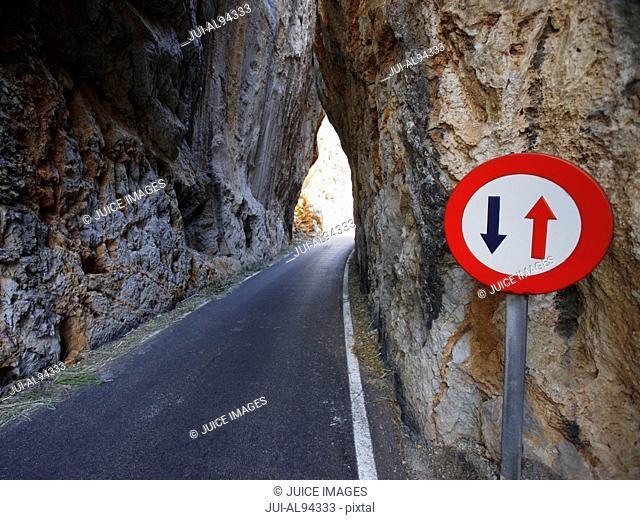 Narrow street with traffic sign between rocks near Torrent de Pareis, Mallorca, Spain