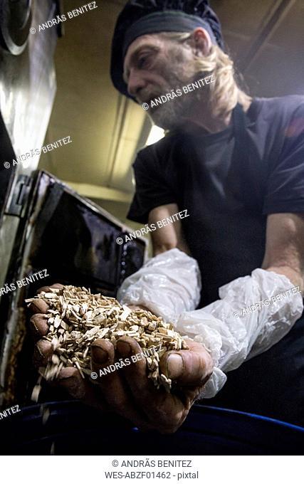 Fish smoker putting beechwood chips into smoker