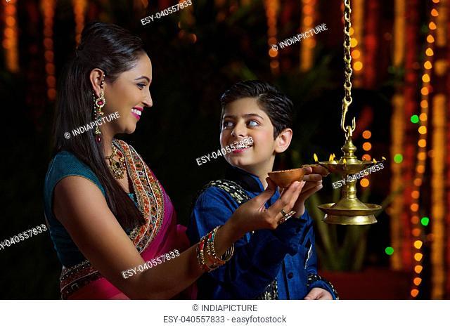 Mother and son lighting diyas