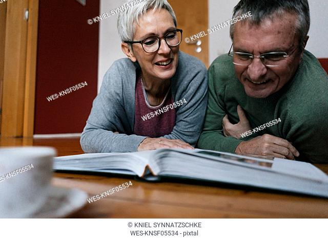 Senior couple lying on the floor at home looking at photo album