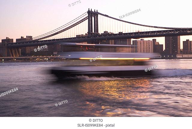 Boat in motion on East River by Manhattan Bridge, New York City, USA