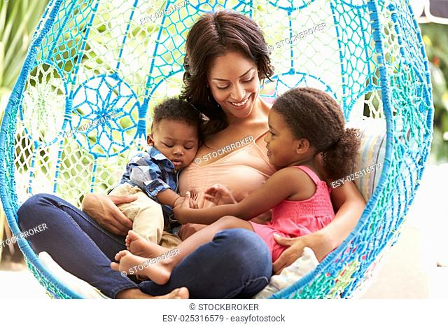 Mother With Children Relaxing On Outdoor Garden Swing Seat