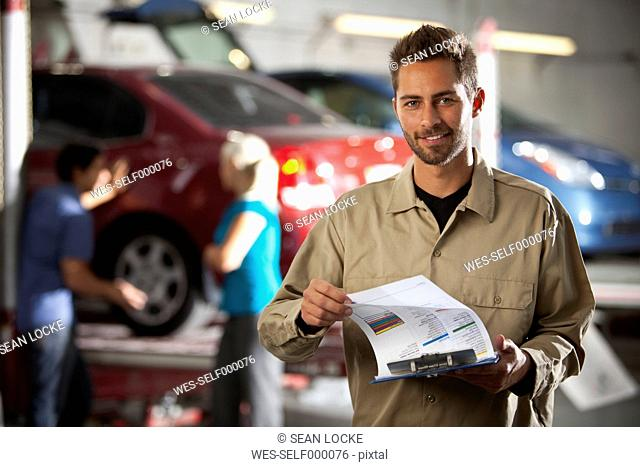 Smiling man in repair garage holding clipboard with ckeck list