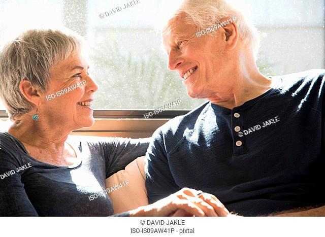 Senior couple sitting together, face to face, smiling