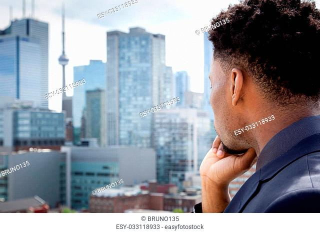 Attractive afro-american business man posing in studio in front of downtown Toronto