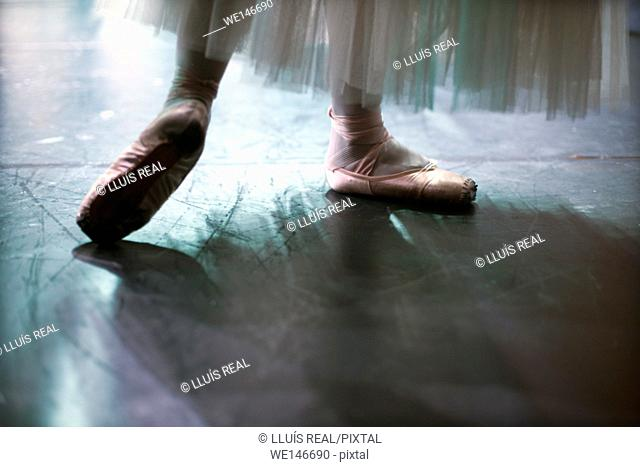 close-up of the feet of a classical ballet dancer dancing on a stage in a theater