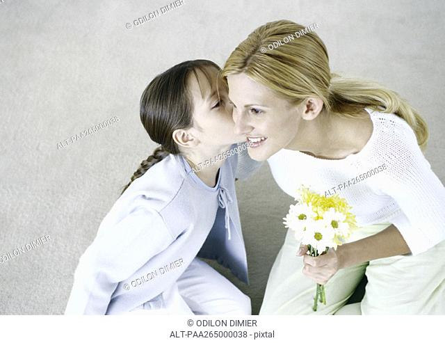 Woman holding bouquet of flowers, girl kissing her cheek