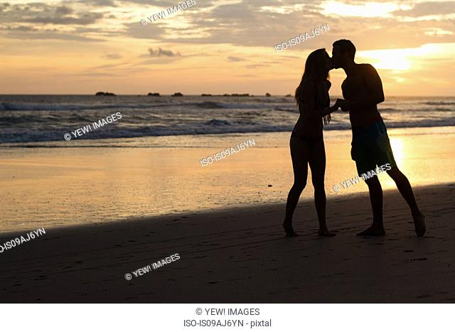 Silhouette of romantic couple kissing on beach, Nosara, Guanacaste, Costa Rica