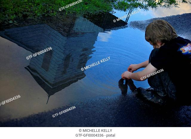 Boy kneeling playing in puddle of water reflecting church