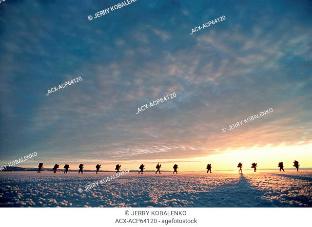 Skiers on frozen Frobisher Bay near Iqaluit, Nunavut, at sunrise in midwinter, Canada
