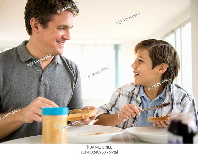 Father and son (8-9) eating lunch