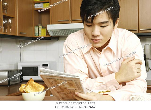Close-up of a young man reading a newspaper at a kitchen counter
