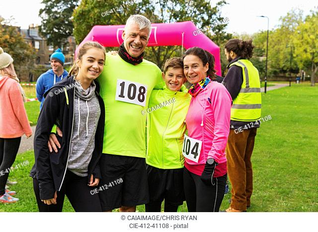 Portrait smiling family runners at charity run in park