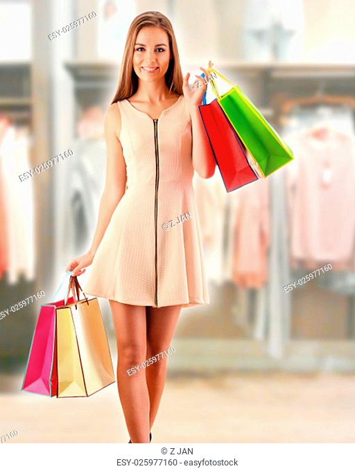 Young woman with shopping bags in shopping mall