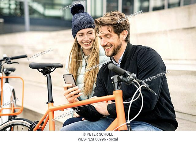 Smiling couple with bicycles and cell phone in the city