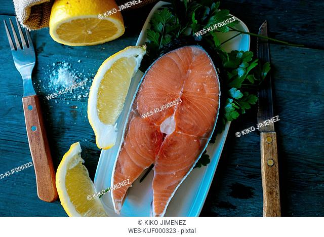 Raw salmon fillet on plate with cutlery, salt and lemon