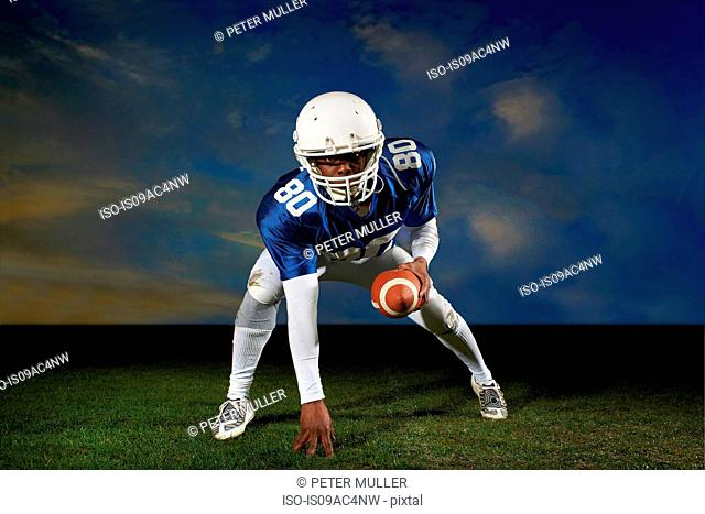 American football player leaning forward with hand on grass