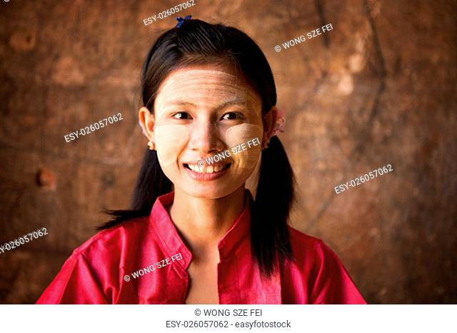Young Myanmar female with Thanaka, a yellowish-white paste made from ground bark and used as a cosmetic and for sunburn protection