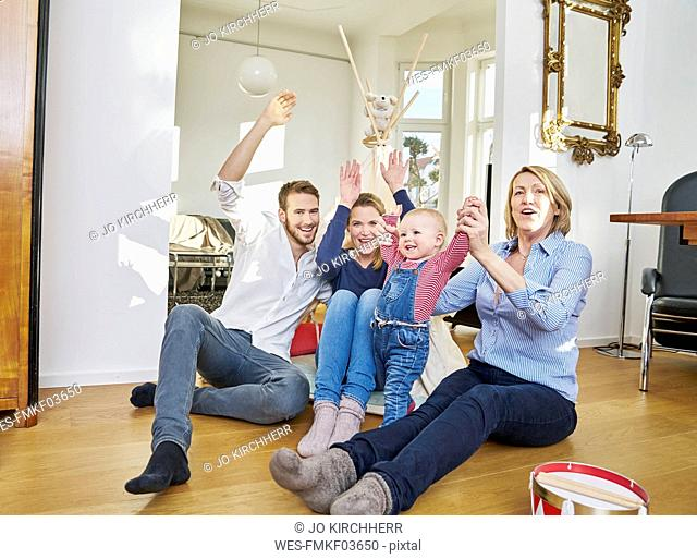 Happy familiy with baby girl playing in living room