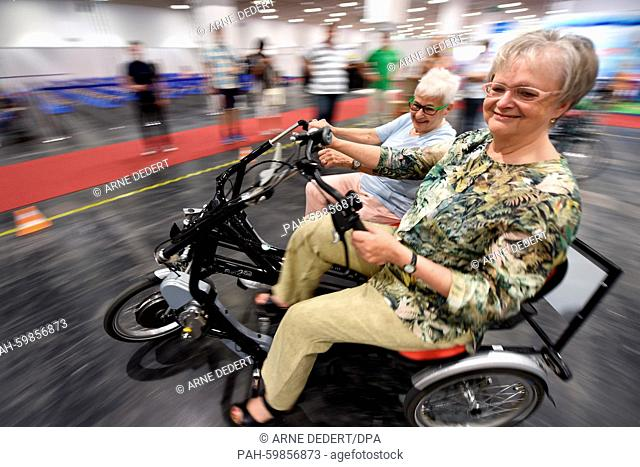 Gunda Krauss (L) and Rosemarie Killius ride a parallel tandem bicycle on a test course at the trade show for senior citizens SenNova inFrankfurt am Main