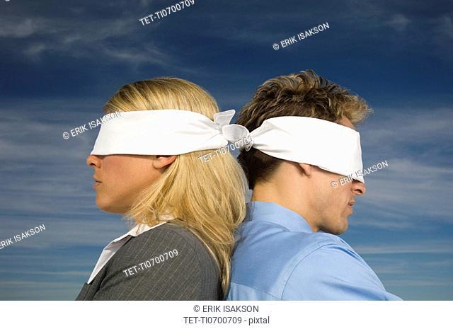 Blindfolded businesspeople standing back to back, Salt Flats, Utah, United States