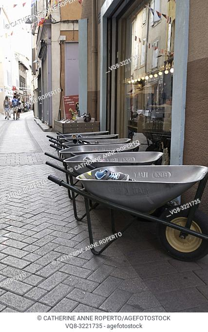 Row of horizontal wheelbarrows with shoes and trainers, and ropes of fairy lights and bunting, with tourists in the distance in L'Isle sur la Sorgue, Provence
