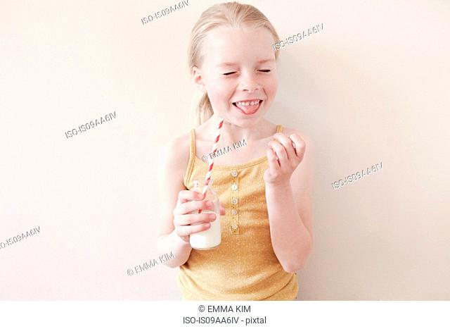 Young girl sticking tongue out and holding glass of milk