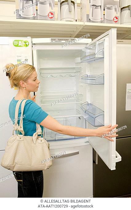 Woman is buying a refrigerator