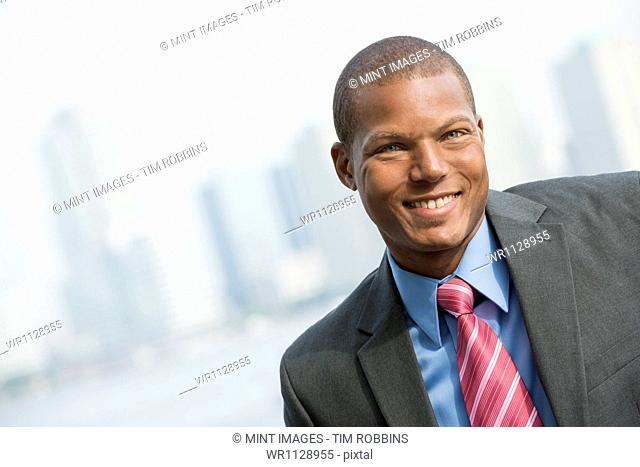 A young man in a business suit with a blue shirt and red tie. On a city street. Smiling at the camera